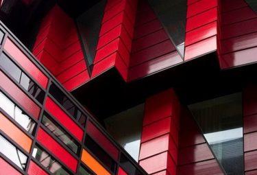 Красно-бордовый фасад необычного здания Kugen