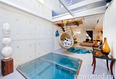 Бассейн в гостиной квартиры покрыт стеклянным экраном