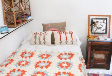 Спальня в многоуровневой квартире с вязаным пледом на кровати