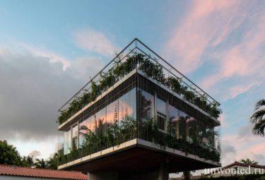 Скульптурный дом с вьющимся зеленым фасадом