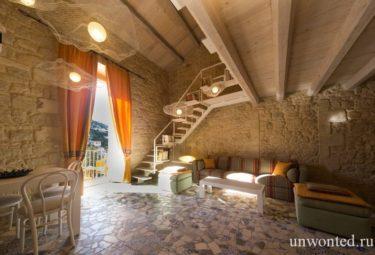 Лестница на верхний уровень лофта с древними каменными стенами